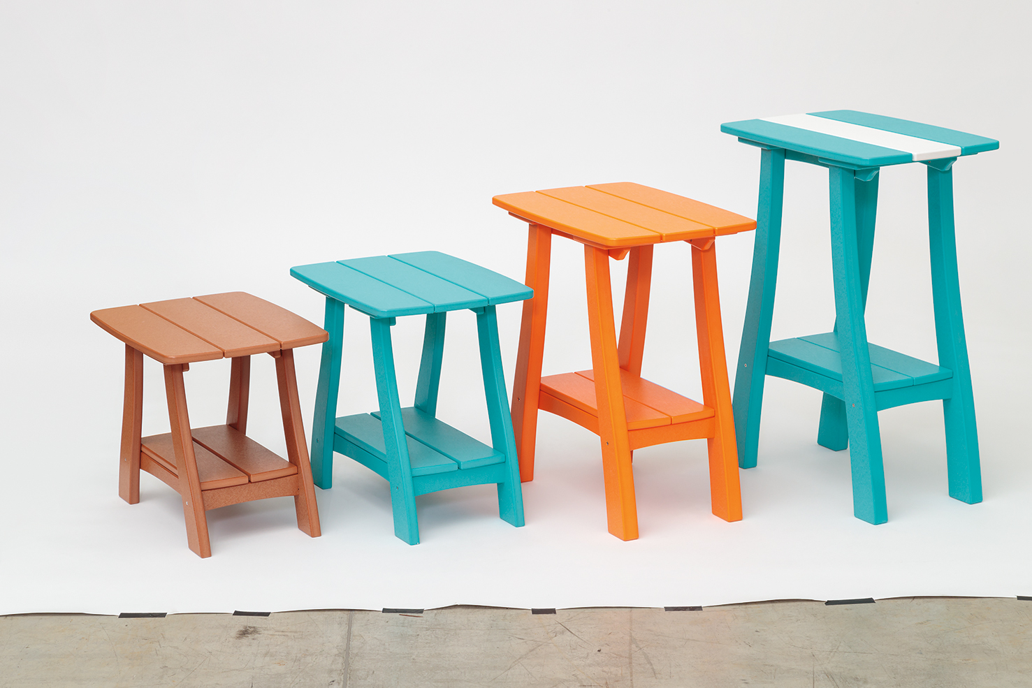 four brightly colored square tables side by side